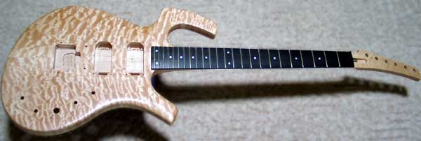 Electric guitar using a commercially produced neck mounted on curly maple. Click the image for an enlarged view.